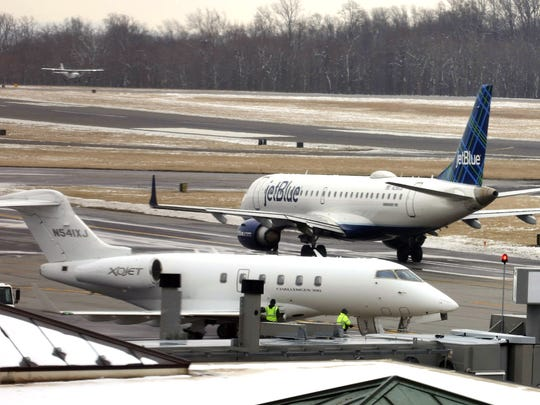 A private plane lands as a JetBlue plane taxies before takeoff at Westchester County Airport Jan. 30, 2018.