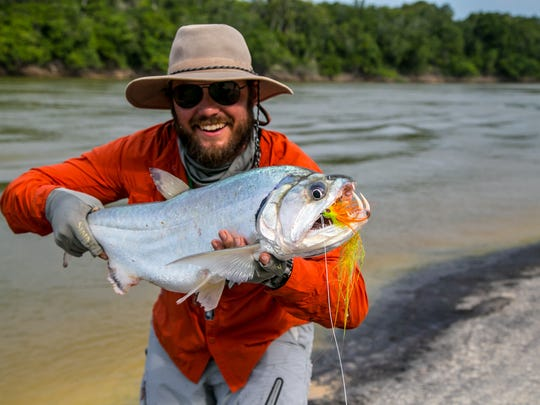 Kyle Zempel with a payara, or vampire fish, which he