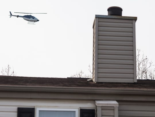 A helicopter circles overhead after a police officer