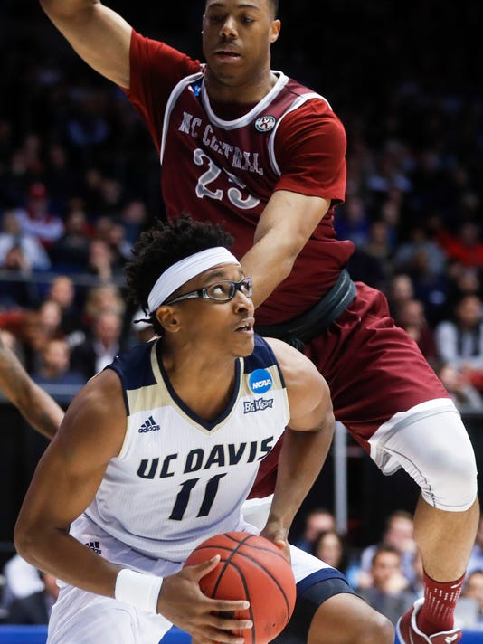 UC Davis' Chima Moneke (11) eyes the basket as North Carolina Central's Kyle Benton (25) defends during the second half of a First Four game of the NCAA men's college basketball tournament, Wednesday, March 15, 2017, in Dayton, Ohio. UC Davis won 67-63. (AP Photo/John Minchillo)