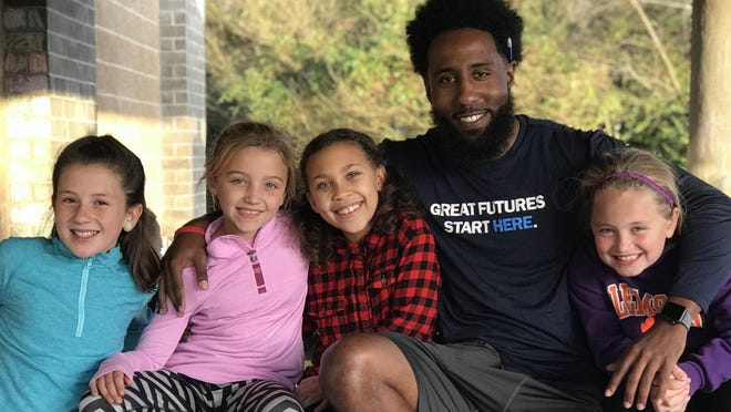 Former Brevard College football player DeVon Holmes, the Health and Wellness Director at the Cindy Platt Boys & Girls Club of Transylvania County, poses with some of his kids that he coaches.