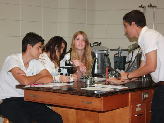 Rapides High students (from left) Lucas Lima, Luz Rubio, Jule Tiedemann and Victor Pires try out new microscopes on Tuesday. The new equipment features the latest technology and was purchased through funds from the Rotary Club of Lecompte and its supervising district headquarters.