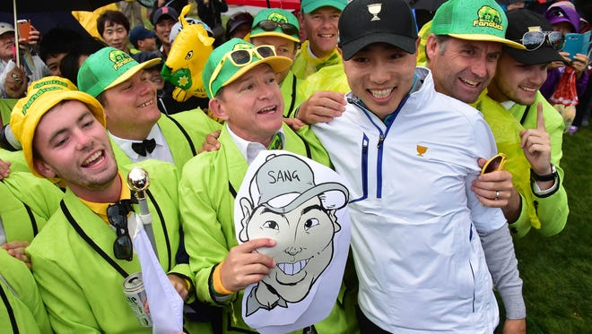 Bae Sang-Moon of South Korea (R) celebrates his team's win with the International Team supporters on the 13th hole during the fourth round of fourball matches of the 2015 Presidents Cup at the Jack Nicklaus Golf Club in Incheon on Oct. 10, 2015.