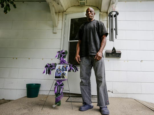 Tracie Rose poses for a photo in from of his house in Flora, Ind., on Wednesday, July 5, 2017. Next to him is a cross with photos of his four granddaughters - Photos of the four children - Keyana Davis, 11, Keyara Phillips, 9, Kerrielle McDonald, 7, and Kionnie Welch, 5 - who were killed in a November house fire in Flora, Ind.