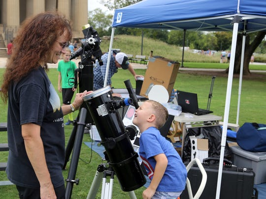Theo Wellington, an astronomy enthusiast and president of the Barnard-Seyfert Astronomical Society, helps Brody Marbach view the sun through a solar telescope at an eclipse party she hosted Sunday August 21, 2016 at Centennial Park to give information on viewing next year's solar eclipse.