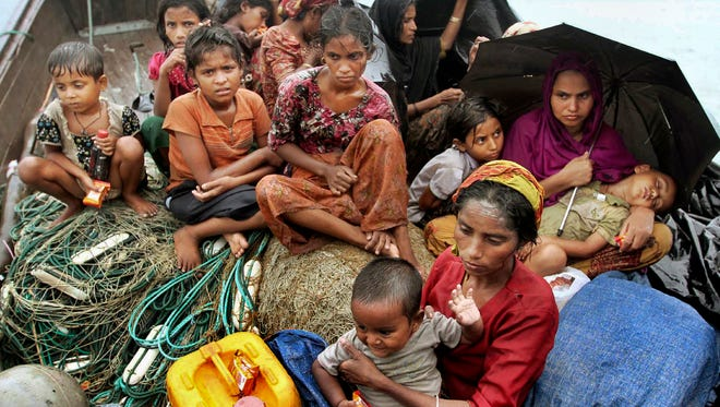 In this June 13, 2012, file photo, Rohingya Muslims who fled Myanmar to Bangladesh to escape religious violence, sit in a boat after being intercepted crossing the Naf River by Bangladeshi authorities in Taknaf, Bangladesh. Asia's more than 1 million ethnic Rohingya Muslims are considered by rights groups to be among the most persecuted people on earth. Two recent shipwrecks in the Mediterranean Sea believed to have taken the lives of as many as 1,300 asylum seekers and migrants has highlighted the escalating flow of people fleeing persecution, war and economic difficulties in their homelands. (AP Photo/Anurup Titu, File)