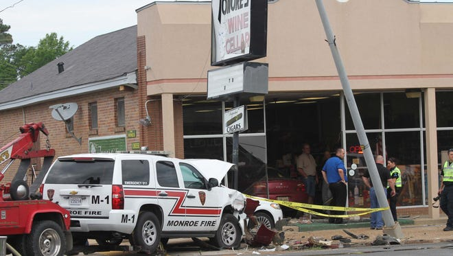 A two-vehicle accident on Louisville Avenue sends a car crashing through the front of Tonore's Wine Cellar on Wednesday.