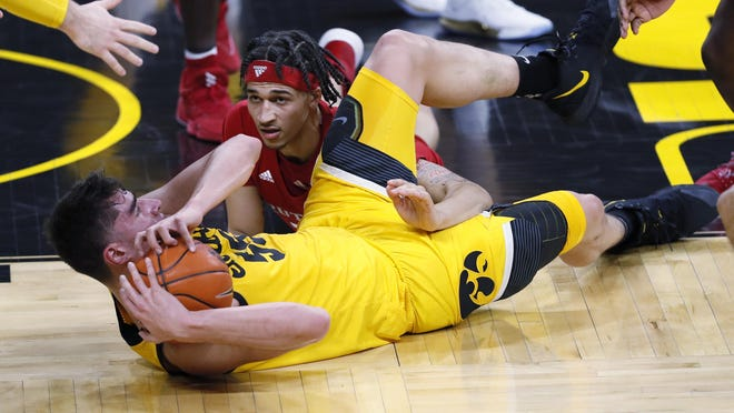 Iowa center Luka Garza, left, fights for a loose ball with Rutgers guard Caleb McConnell during the first half of game ON Wednesday, Jan. 22, in Iowa City, Iowa.