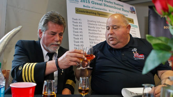 Belle of Louisville Captain Mark Doty, left, toasts with Belle of Cincinnati Captain Alan Bernstein after the Great Steamboat Race Four Roses bourbon tasting and rules announcement Wednesday morning. The race is scheduled for April 29. By Matt Stone, The C-J April 8, 2015.