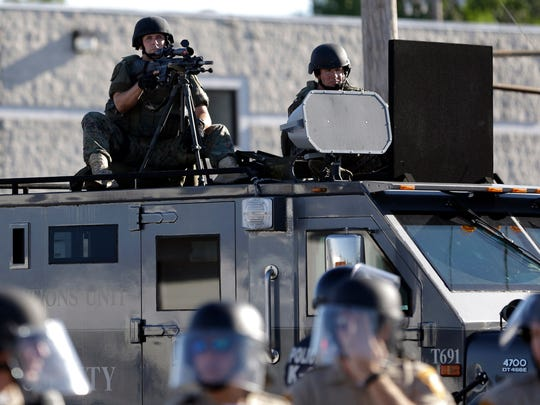 In this Aug. 9, 2014, file photo, a police tactical team moves in to disperse a group of protesters in Ferguson, Mo.