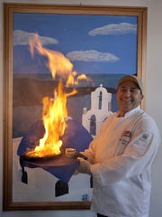 Taki Sawi, shown in 2009 with an order of flaming Saganaki, at Santorini Greek Kitchen.