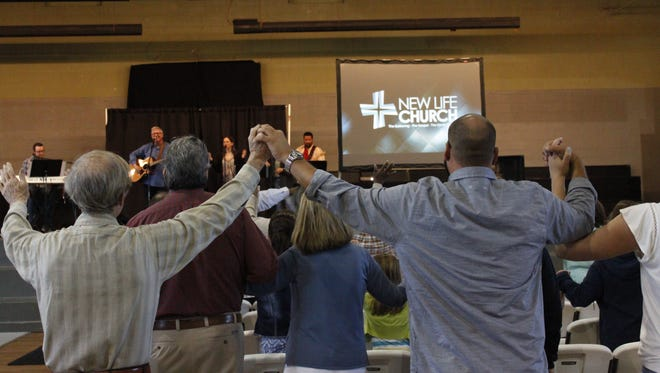 Church attendees hold hands during New Life Church's service Sunday.
