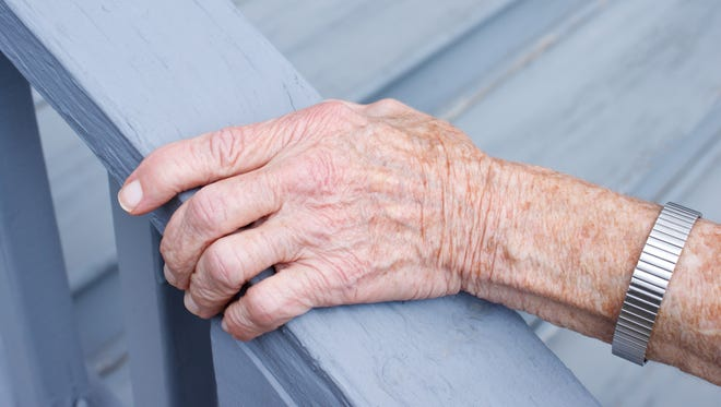 Senior lady holding stair rail in porch
