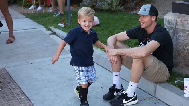 Patrick Reeve, 3, and his father, Tommy III, wait for the ASU Oct. 28 ASU homecoming parade to begin. The family is walking with a family friend in support of Down Syndrome.