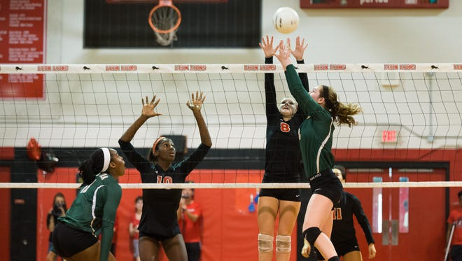 Leon freshman Makayla Washington (left) and senior Ashley Dodson (right), wearing black, go for the block against Lincoln's combo of setter Loren Scott (right) and middle hitter Veresia Yon (left).