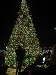 People snap photos in front of the lit Christmas tree