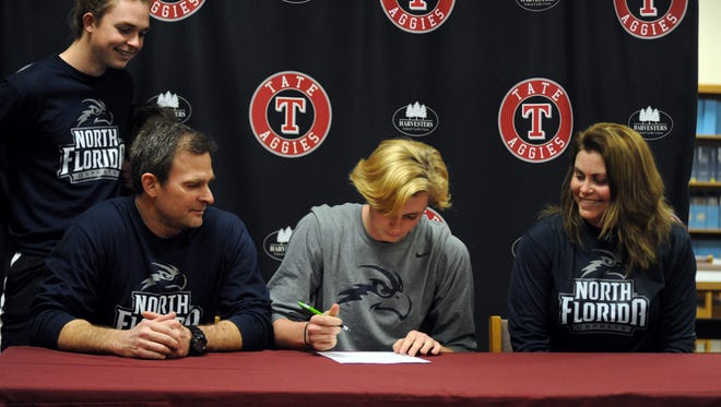 Tate senior LJ Estes (center, gray) signs an athletic scholarship to play soccer with the University of North Florida while surrounded by (from left) his younger brother Jake, father Joe and mother Tanya at J.M. Tate High School on Feb. 8, 2017.