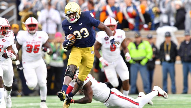 Fighting Irish running back Josh Adams (33) runs the ball as North Carolina State Wolfpack safety Jarius Morehead (31) defends in the first quarter at Notre Dame Stadium.