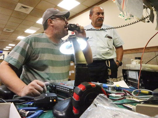 Ricardo Rosario, left, talks on the CB Radio while working with Joel Rodriguez at the Bandidos Radio Shop inside the Petro Stopping Center at I-10 and Horizon Blvd. They cater mostly to truck drivers who depend on CB radios for their work.