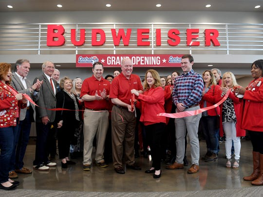 Mike McWherter is joined with his wife Mary Jane as they cut the ribbon at Central Distributors during their grand opening, Thursday, April 26, in Jackson. Hundreds of people gathered for the grand opening and ribbon cutting as well as to see the Budweiser Clydesdales.