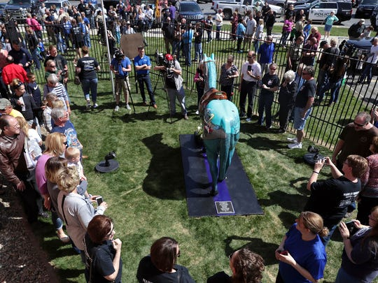 More than 200 people gather outside the Squirrel Cage Jail to honor the late Pottawattamie County Sheriff's Deputy Mark Burbridge with the Horses of Honor statue at the Pottawattamie County public art exhibit on Saturday, April 28, 2018 in Council Bluffs, Iowa.
