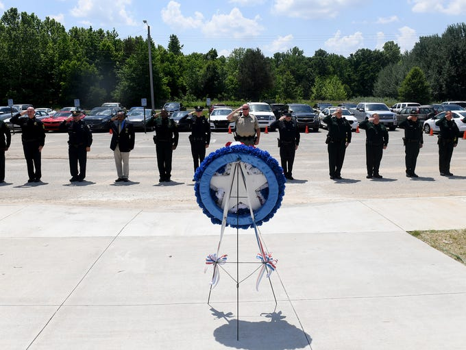 Law enforcement officers stand in salute during a local