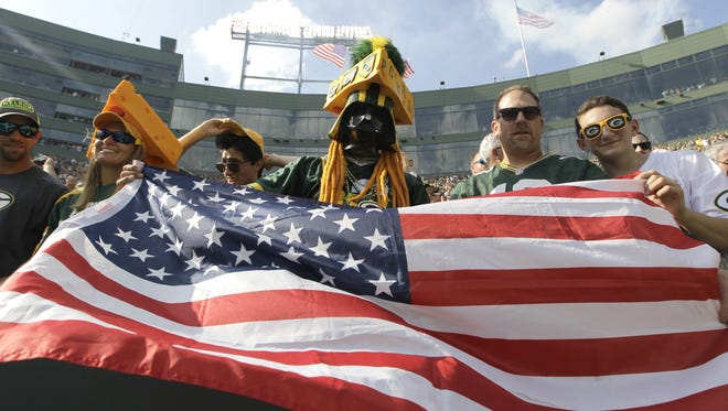 Green Bay Packers fans wave the American flag following the National Anthem before their Sept. 24 game against the Cincinnati Bengals.