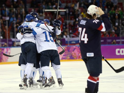 Finland defenseman Juuso Hietanen (38) celebrates with teammates after scoring a goal as USA forward T.J. Oshie (74) skates away. Finland beat the USA 5-0 to win bronze.
