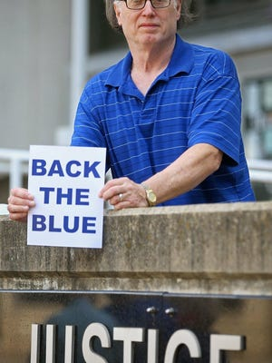 Jim Collver holds a print of what he would like to paint on High Street in front of the Harold K. Stubbs Justice Center, Friday, Aug. 07, 2020, in Akron, Ohio.