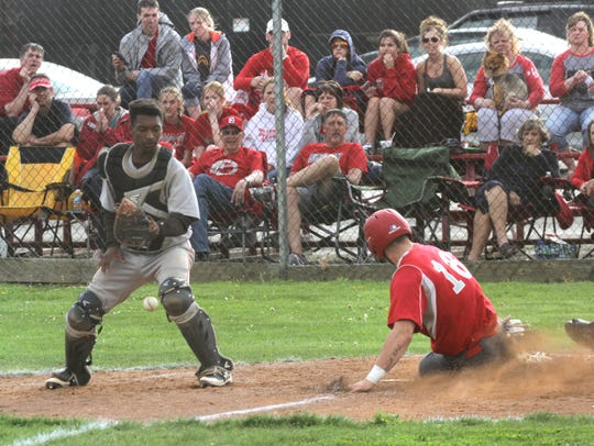 Shelby's Carter Brooks slides into home plate as Mansfield