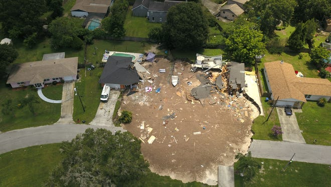 In this aerial photo, debris is strewn about July 14, 2017, after a sinkhole damaged two homes in Land O' Lakes, Fla. The hole opened up just before 7:30 a.m. ET and expanded to this size by mid-afternoon