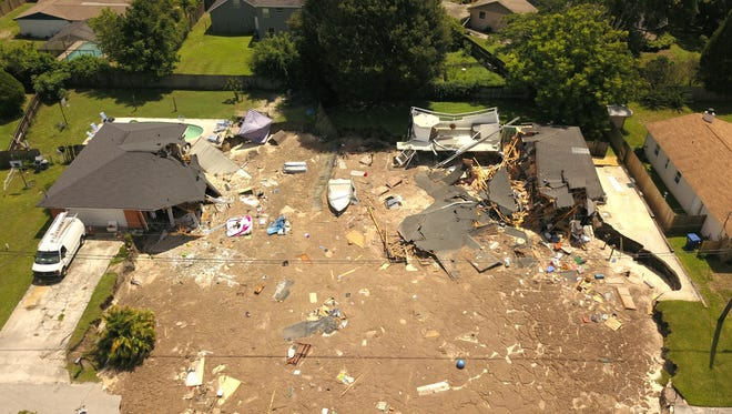 In this aerial photo, debris is strewn about after a sinkhole damaged two homes in Land O' Lakes, Fla. on Friday, July 14, 2017. The sinkhole, which started out the size of a small swimming pool and continued to grow, swallowed a home in Florida and severely damaged another.