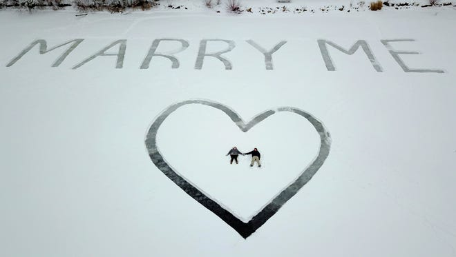 In this Jan. 7, 2018 photo provided by Ed Becker, Gavin Becker and his long-time girlfriend Olivia Toft lay in the snow after he proposed on Eight Crow Wing Lake near Nevis, Minn. Becker had his family's help etching out the big question with a snow blower in 25-foot-tall letters and a huge heart in the snow on the frozen lake. Then Gavin rented a plane and took Toft, who said yes, for a ride over the lake to see where his father took photos of the event.