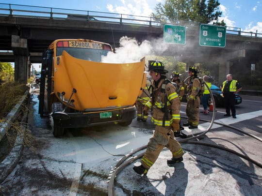 Firefighters douse the engine compartment of a Mountain