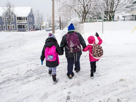 Angela Cross walks her daughters Jasmine, age 8, left, and Christy, age 6, to school at the Sustainability Academy in Burlington on Thursday, February 16, 2017.