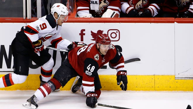 Arizona Coyotes left wing Jordan Martinook (48) falls to the ice as he tries to keep the puck away from Devils left wing Taylor Hall (9) during the game Saturday, March 11, 2017, in Glendale, Ariz.The Devils lost their 10th straight game.