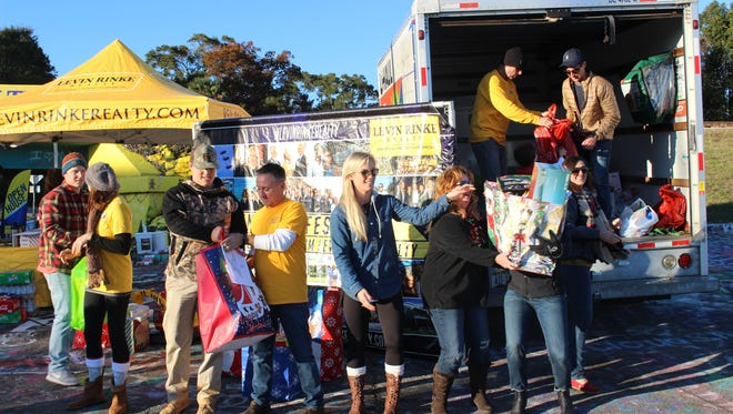 A team from Levin Rinke Realty loads a truck with toys collected at the 2017 Toy Drive on Dec. 9.