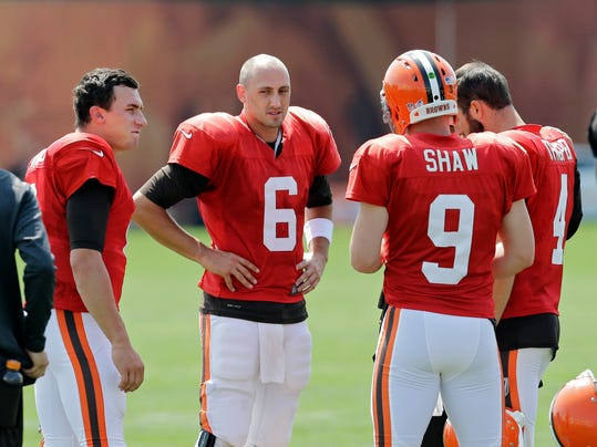 Cleveland Browns quarterbacks Johnny Manziel, left, Brian Hoyer (6), Connor Shaw (9) and Tyler Thigpen talk during practice at NFL football training camp in Berea, Ohio Wednesday, Aug. 6, 2014. Coach Mike Pettine is expected to name his starting quarterback for Saturday night's exhibition opener in Detroit. Hoyer is listed first on the team's depth chart, but rookie Manziel may be gaining on him. (AP Photo/Mark Duncan)
