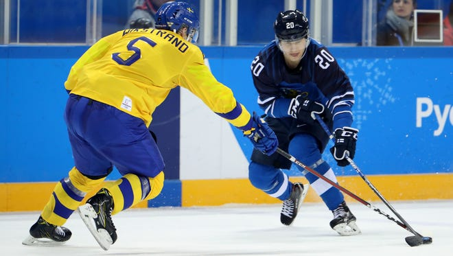 Sweden defenseman Mikael Wikstrand (5) defends against Finland forward Eeli Tolvanen (20) in a hockey game between Sweden and Finland during the Pyeongchang 2018 Olympic Winter Games at Kwandong Hockey Centre.
