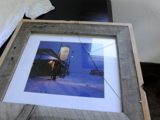 Broken glass in a picture frame that was knocked off the wall at Gordon Becker's home in Lincoln during Thursday morning's string of earthquakes.