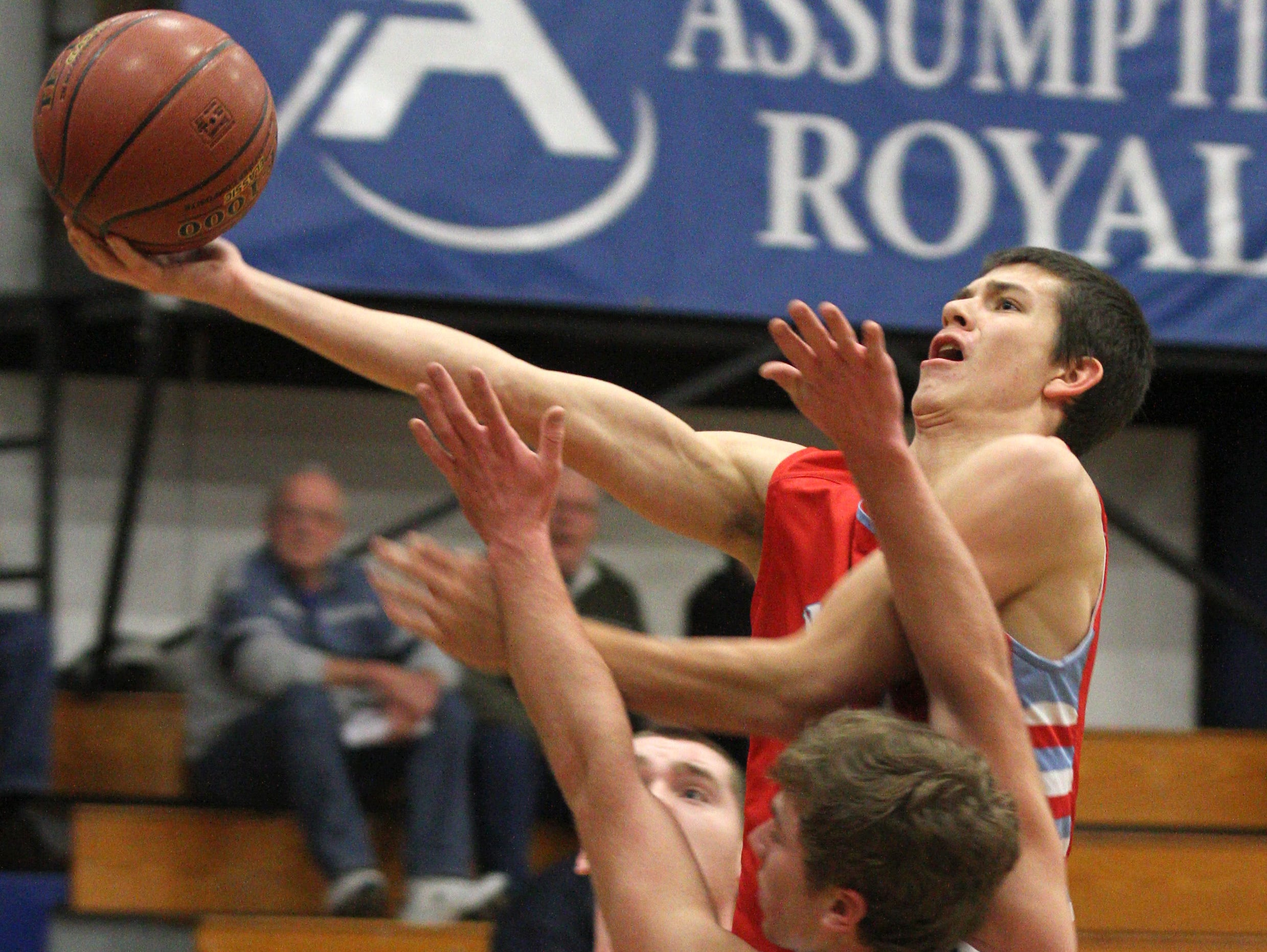 Wausau Newman junior forward Jake Gajewski gets a one handed shot off while Brady Baltus of Assumption defends in the game against Assumption held in Wisconsin Rapids Tuesday night.