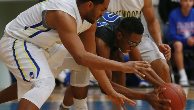 Americas' Jamaure Gregg, center, battles Eastwood's James Williams, left, and Richie Rodriguez for a loose ball during the third quarter Friday at Eastwood.