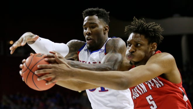 Kansas forward Jamari Traylor, left, fights for a rebound with Austin Peay center Chris Horton during the first half of a first-round men's college basketball game in the NCAA Tournament, Thursday, March 17, 2016, in Des Moines, Iowa.
