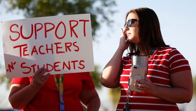 """Stefanie Lowe, right, wipes away a tear as she talks with fellow teacher Nanette Swanson, as they join teachers, parents and students at Tuscano Elementary School to stage a """"walk-in"""" for higher pay and school funding on April 11, 2018, in Phoenix. Teachers gathered outside Arizona schools to show solidarity in their demand for higher salaries staging """"walk-ins"""" at approximately 1,000 schools that are part of a statewide campaign for a 20 percent raise and more than $1 billion in new education funding."""