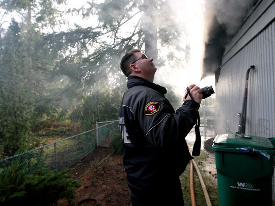Bremerton Fire Marshal Mike Six works the scene of a residential structure fire on Pinecone Drive in Bremerton on Friday, Dec. 30, 2016.