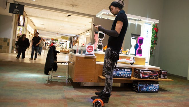 Patrick Edney rides around on a hoverboard at a kiosk in the Asheville Mall. Edney rides on a hoverboard in an effort to sell them to inquisitive customers.
