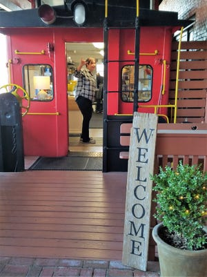 His spot is too cute. Harry and Lola's employee Amanda Hancock waves from inside the adorable caboose.