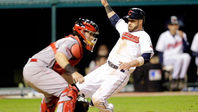 Cleveland Indians' Jason Kipnis, right, scores on an RBI-double hit by Carlos Santana in the seventh inning of a baseball game against the Cincinnati Reds, Friday, May 22, 2015, in Cleveland. Reds catcher Tucker Barnhart, left, waits for the ball.