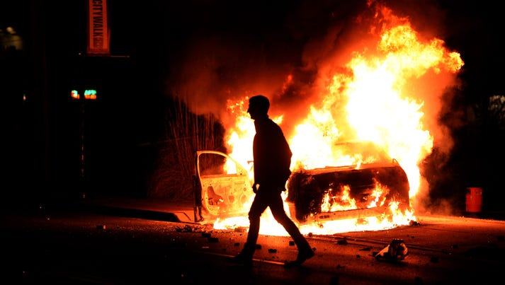 A man walks past a burning police vehicle during clashes