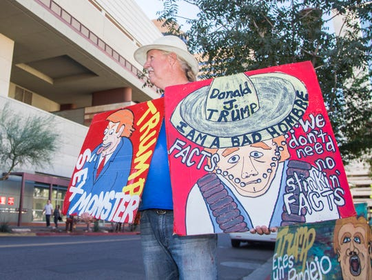 Rob McElwin of Phoenix holds up signs before a Trump